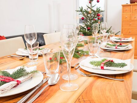 trees services: table with glasses, plates, cutlery and Christmas tree