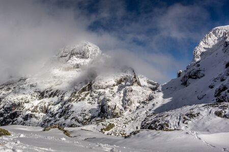 The peak in the clouds, a beautiful day after a winter storm at the Rila mountain in Bulgaria, Maliovica. 写真素材 - 134822865