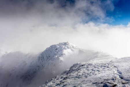 Maliovica peak in the mists of the clouds at the Rila mountain in Bulgaria.