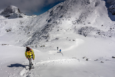Women climbing the summit at winter and she is being followed by two climbers at the Rila mountain in Bulgaria, Maliovica. 写真素材 - 134815687