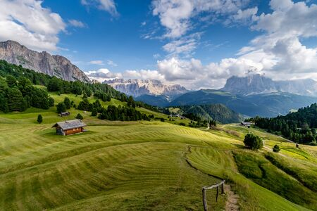 The green grass fields and a hut at the beautiful Val Gardena valley in Dolomites mountains, Alps, Italy.