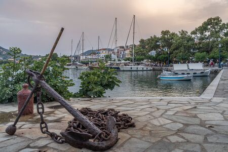 Anchor and yachts at the port at sunset at Skopelos island in Greece.