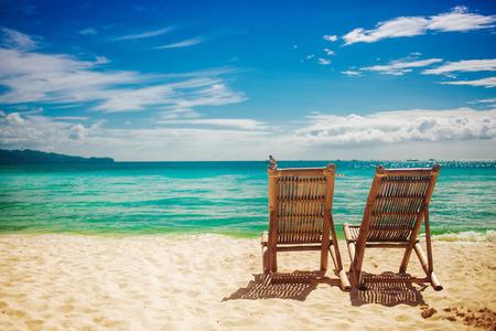 clima tropical: Dos sentados lugar en una playa tropical Foto de archivo
