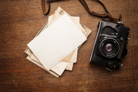 photographic effects: Old retro camera with photo on vintage grunge wooden boards abstract background