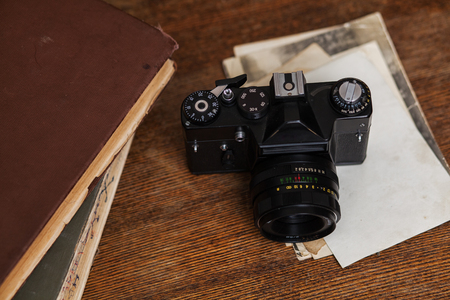 Old retro camera with photo on vintage grunge wooden boards abstract background