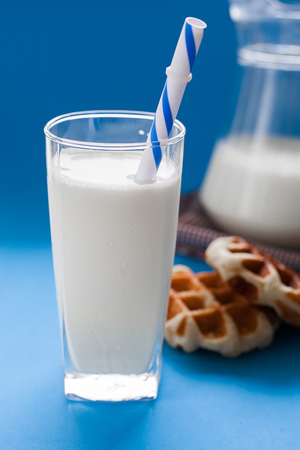 Milk with wafer on blue background, breakfast Stock Photo