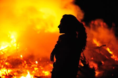 Silhouette in fire of beautiful young woman