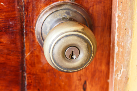 closeup of doorknob with wooden door photo