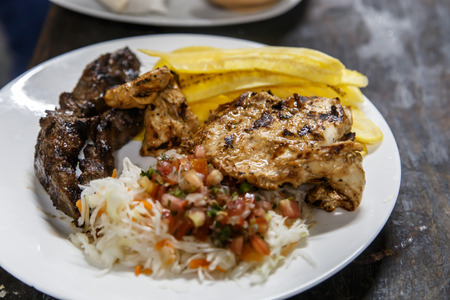 mojo: traditional nicaraguan cuisine, roast meat, salad and fried banana. Stock Photo
