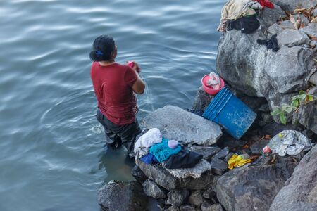 allepey: poor woman from nicaragua washing clothes at water Stock Photo