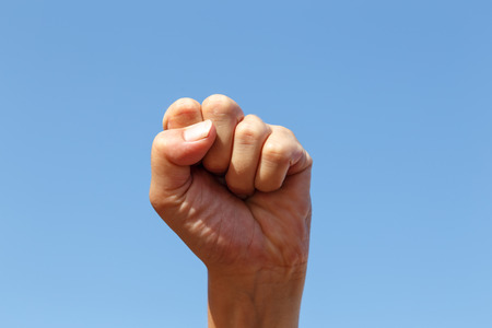close fist: close fist with sky at background Stock Photo