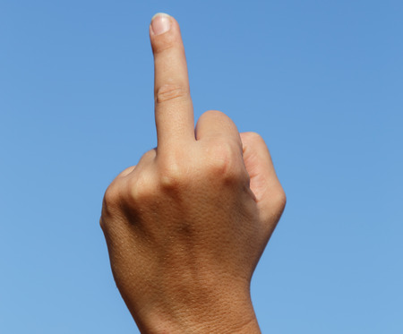 middle finger: middle finger, insult sign with sky at background Stock Photo