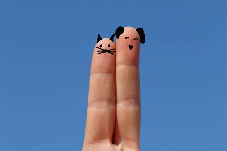 dog and cat, two fingers painted with sky at background Imagens