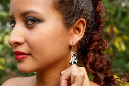 atractive latin woman showing handmade earrings in nature Stock Photo