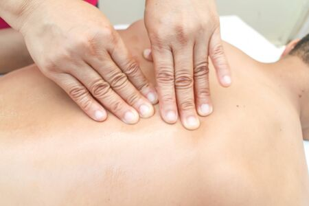 masseur: Masseur doing back massage on man body in the spa