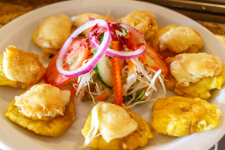 Tostones cup, Crushed fried plantains with beans, onion, tomato and white cheese