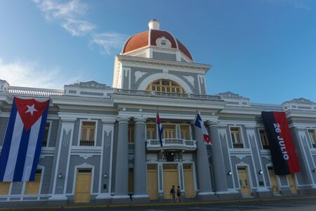 center hall colonial: cienfuegos, cuba. City Hall with cuban and part Flags on facade during celebration of 1 january. Stock Photo
