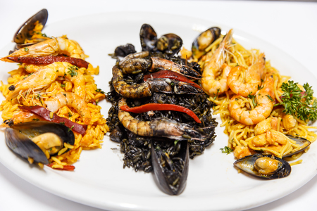 paella, black rice and fideua on same plate. Typical spanish food