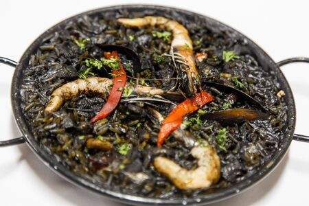 Black risotto with seafood on white plate, arroz negro from spain