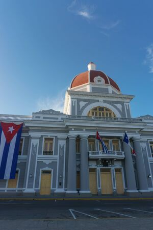 jose: cienfuegos, cuba. City Hall with cuban and part Flags on facade during celebration of 1 january. Stock Photo