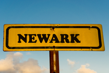Newark city street old antique yellow sign with blue sky at background, USA signal city series.