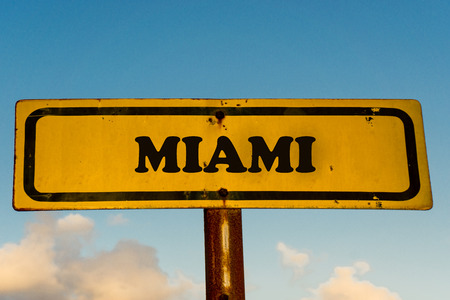 Miami city street old antique yellow sign with blue sky at background, USA signal city series. Banco de Imagens