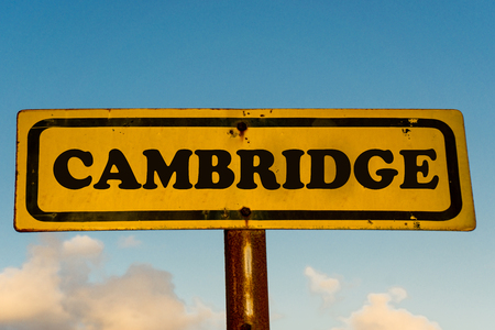 Cambridge city street old antique yellow sign with blue sky at background, USA signal city series.