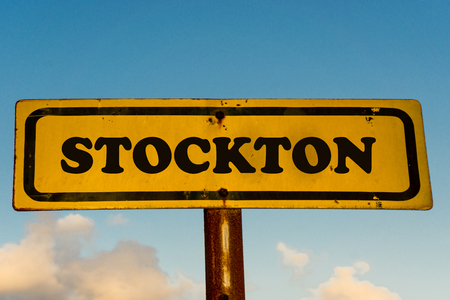 Stockton city street old antique yellow sign with blue sky at background, USA signal city series.