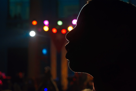 backlit silhouette of a boy with cuba flag in the background