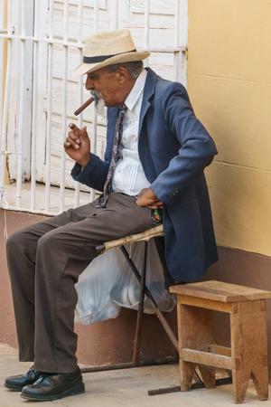 Trinidad, Cuba, January 3, 2017: old man on street smooking a cigar Editoriali