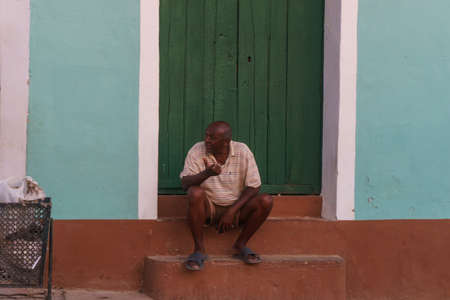 Trinidad, Cuba, January 3, 2017: man on street sitted in front a door