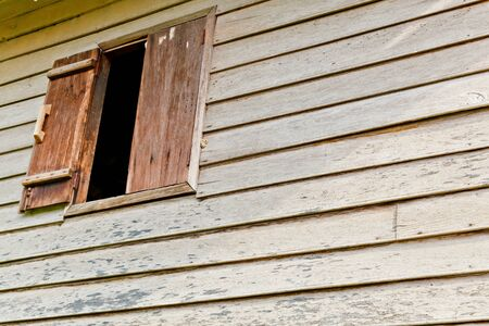 An opened wooden window on the wooden wall Stock Photo