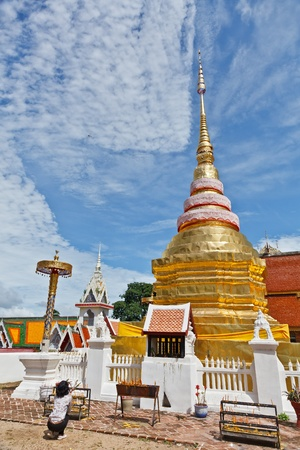 LAMPANG PROVINCE, THAILAND - JULY 17: Unidentified woman pays respect to the golden Pagoda on July 17, 2011 in Pongsanuk Temple, Lampang province, Thailand