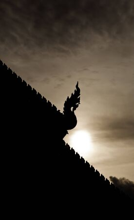 vihara: The silhouette of the Naga on the vihara roof in Phra Singha temple, Chiang Mai province, Thailand Stock Photo