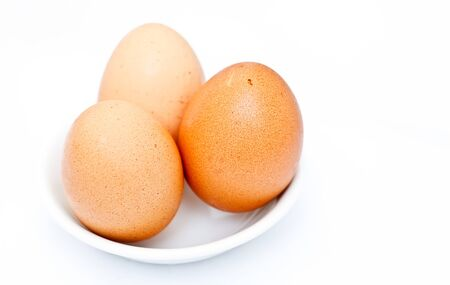 Three Eggs in a Little White Saucer with the Isolated Background photo