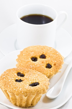 The close up image of two cupcakes and a cup of black coffee photo