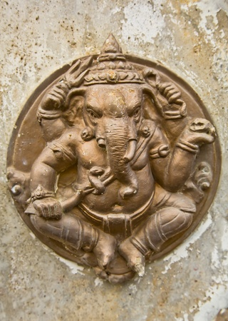 The metallic circle sculpture of the Ganesha on the stone wall Stock Photo