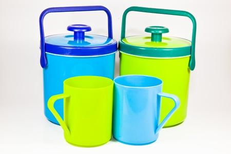 Deux cantines d'eau en plastique color�s et deux tasses en plastique color�s sur fond blanc
