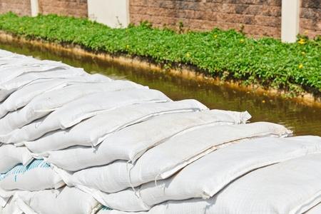 ordelijk: De stapel van witte overlappende ordelijke zandzakken voor de bescherming tegen overstromingen