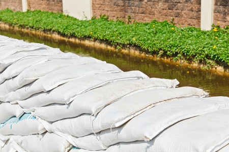 deluge: The pile of white overlapped orderly sandbags for flood protection