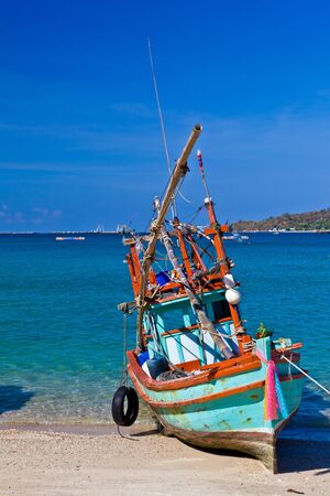 A small colorful wooden fishing boat is run aground on the beach with the background of blue sea photo