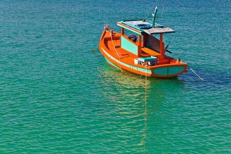 Un petit bateau de p�che en bois color� est flottantes, dans la mer bleue Banque d'images