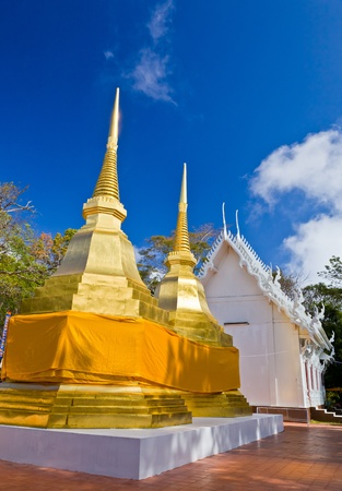Two golden Phra Thats and a white church in Phra That Doi Tung temple, Chiang Rai province, Thailand Stock Photo - 12234780