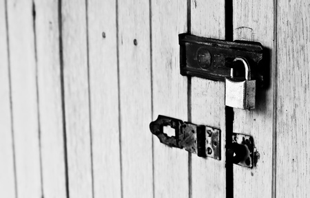 door bolt: The black and white image of the wooden partition is locked with a metalic padlock