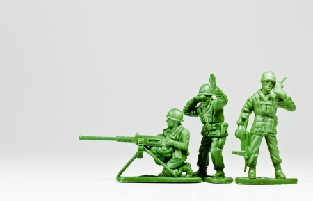 plastic soldier: The isolated image of three green plastic toy soldiers