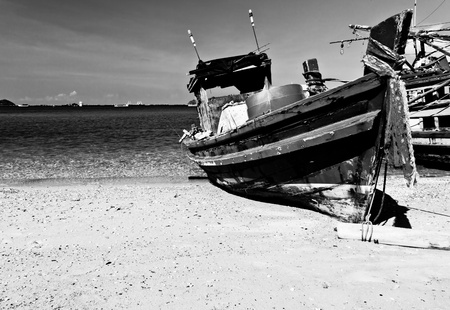 The black and white image of the old wooden fishing boat is parking on the beach, Si-Chang island, Chonburi province, Thailand Stock Photo