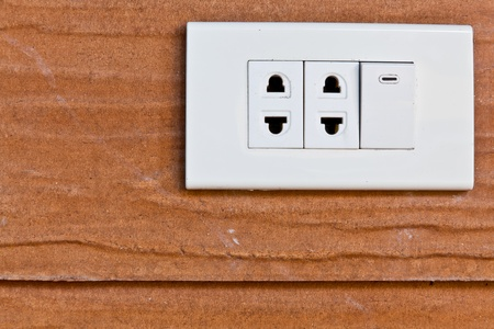 The closeup image of the old sockets and switch on the wooden wall photo