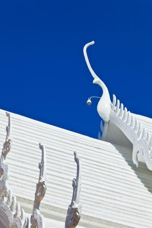 The naga on the top roof of Thai style church at Wat Phra That Doi Tung, Chiang Rai province, Thailand photo