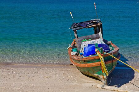 A small wooden fishing boat is parking on the beach, Si-Chang island, Chonburi province, Thailand