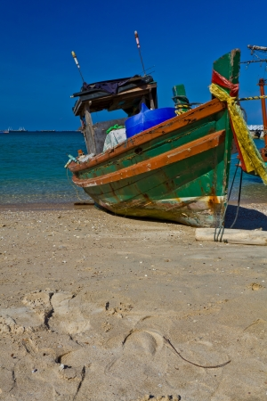 A small wooden fishing boat is run aground on the beach, Si-Chang island, Thailand photo
